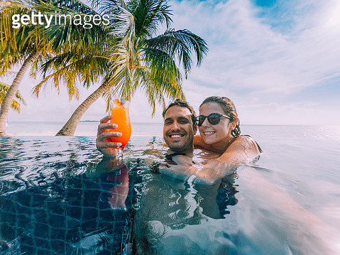 Young adult couple doing a selfie in the swimming pool in a paradisiac island - gettyimageskorea