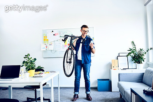 Smiling businessman carrying bicycle in office looking at smartphone - gettyimageskorea