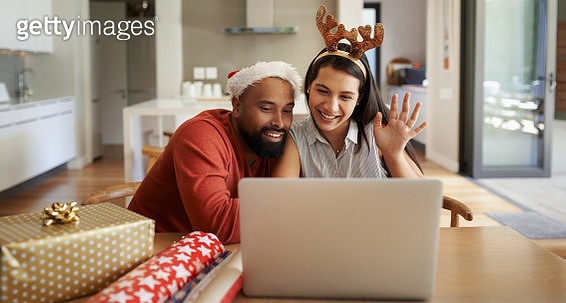 Shot of a happy young couple using a laptop during the Christmas holidays at home - gettyimageskorea