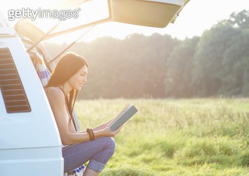 Woman reading book in camper van. - gettyimageskorea