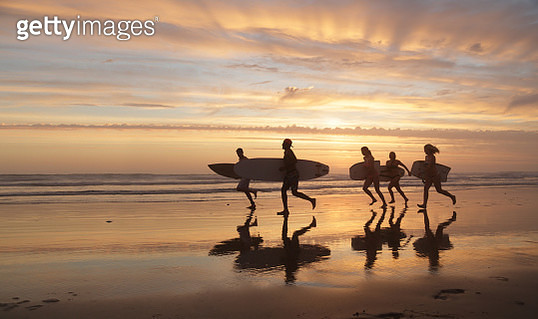 Group of young people walking on beach at sunset with boards - gettyimageskorea