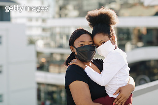 Beautiful & delighted daughter and mother wearing black and white face masks on a rooftop - gettyimageskorea