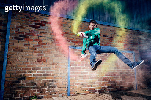 Portrait male modern dancer performing with spray paint against brick wall - gettyimageskorea