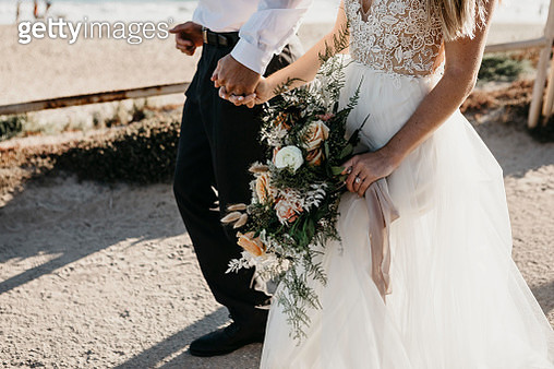 Close-up of bride and groom walking on path at the coast - gettyimageskorea