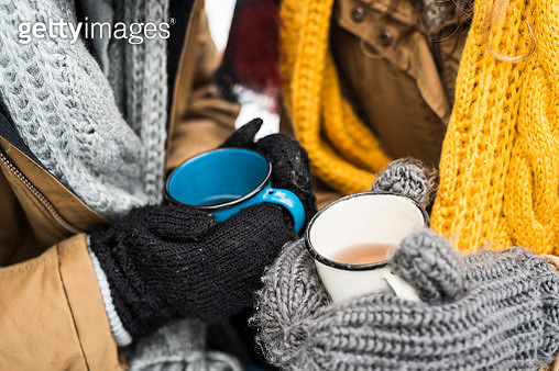 Young couple wearing gloves holding cups of tea in winter, close-up - gettyimageskorea