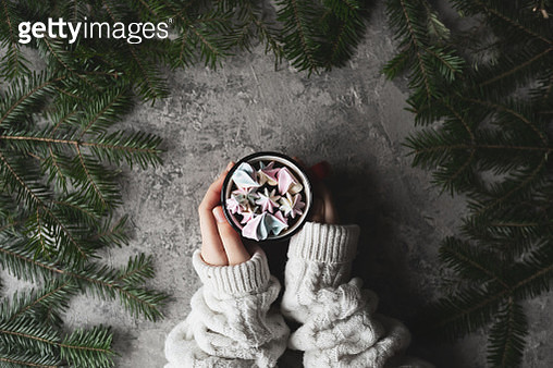 Female hands holding coffee cup, christmas gift boxes and snow fir tree above wooden table. Top view with copy space - gettyimageskorea