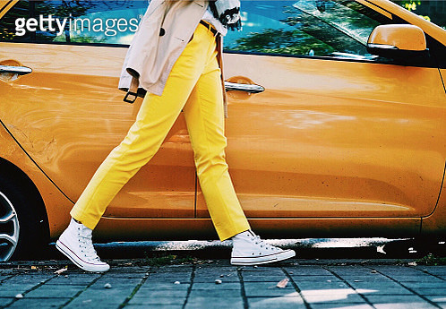 Woman in yellow trousers walking past an orange car - gettyimageskorea