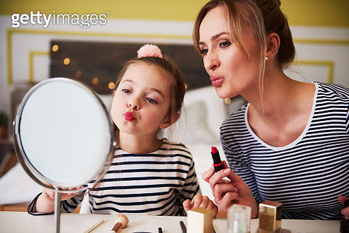Mother and daughter applying make up together, using lipstick - gettyimageskorea