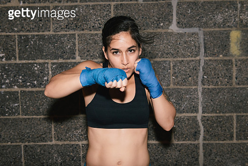 A young brunette woman exercising and boxing punching towards the camera - gettyimageskorea