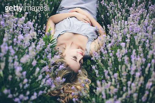 Young and happy blond woman in light purple dress posing on lavender field garden - gettyimageskorea