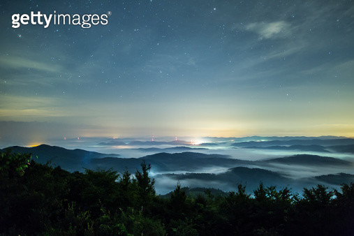 A sea of clouds under the night sky filled with stars.  The mountain tops appear as islands. - gettyimageskorea