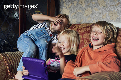 Happy smiling children laughing together using a tablet device - gettyimageskorea