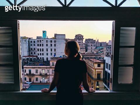 Rear View Of Woman Looking Through Window In City - gettyimageskorea