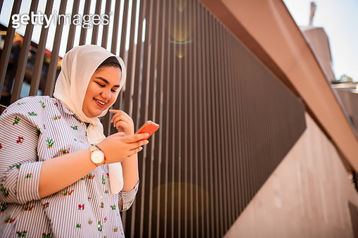 Portrait of a smiling Muslim teenager using mobile phone - gettyimageskorea