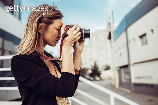 Beautiful young woman using camera and photographing in the city street on a sunny autumn day - gettyimageskorea