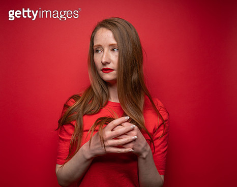 Young woman with red hair on red background - gettyimageskorea