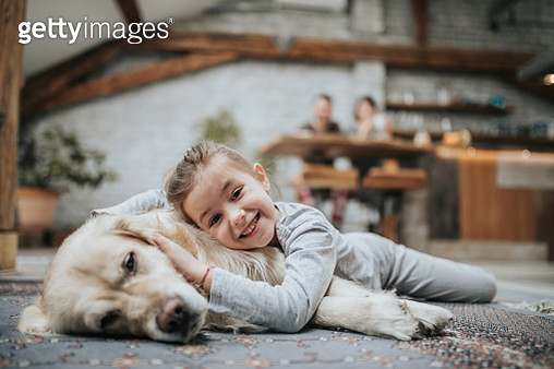 Happy girl enjoying with her dog on carpet at home. - gettyimageskorea