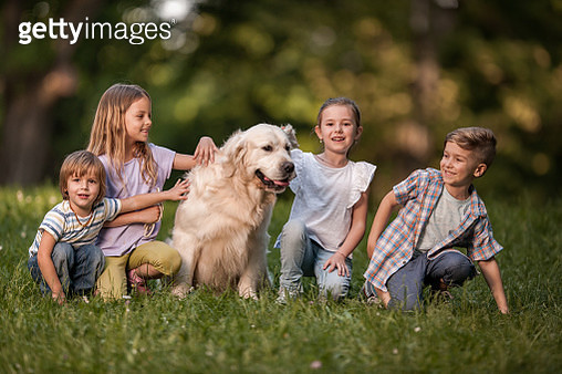 Group of happy kids with golden retriever in spring day at the park. - gettyimageskorea