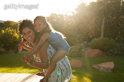 Mother and daughter playing and laughing in their garden - gettyimageskorea