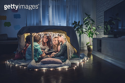 Happy nanny reading stories to small kids in a tent at home. - gettyimageskorea