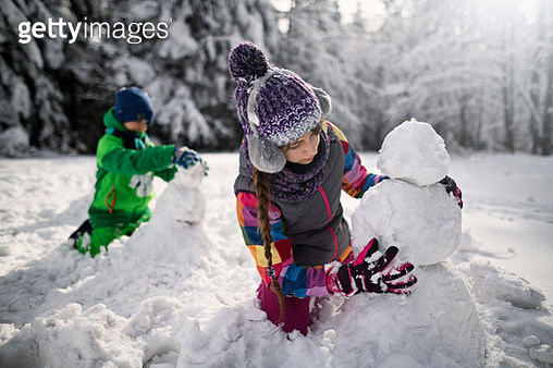 Brother and sister building snowmen in winter forest - gettyimageskorea