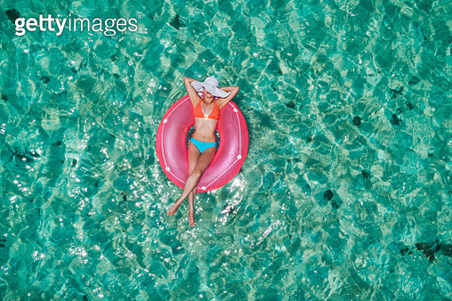 Aerial view of a young women relaxing on inflatable ring in a tropical turquoise pristine beach - gettyimageskorea