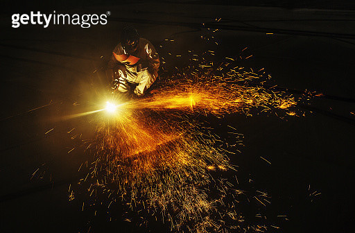 Sparks fly in the dark from a welder in a metal factory. - gettyimageskorea