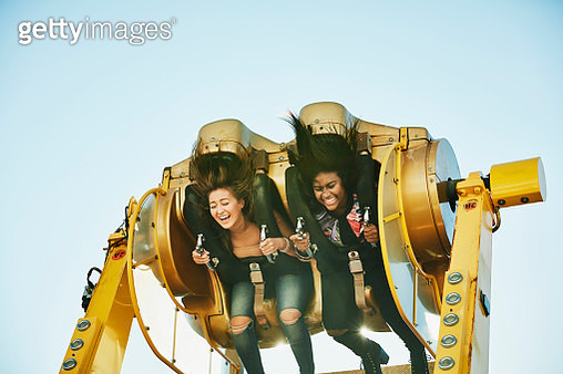 Laughing female friends spinning upside down on amusement park ride - gettyimageskorea