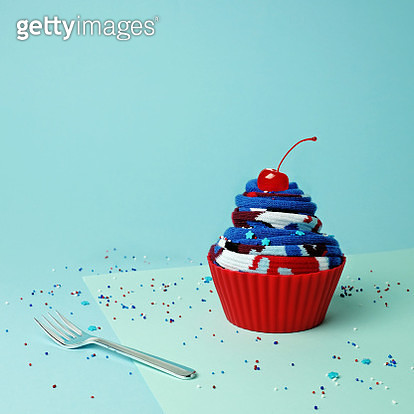 Cupcake made of rolled fabric on a blue background with fork and sprinkles - gettyimageskorea