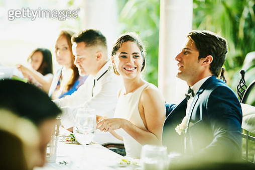 Smiling bride sitting with groom during outdoor wedding reception dinner - gettyimageskorea
