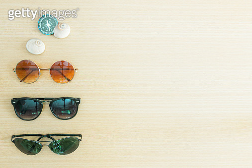 Summer vacation and travel background concept. Sunglasses with compass and seashells on wood table. - gettyimageskorea