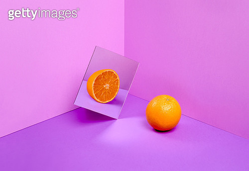 An orange reflecting in a mirror a halved orange over a purple background - gettyimageskorea