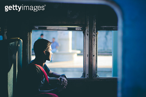 Side View Of Thoughtful Man Looking Through Window In Train - gettyimageskorea
