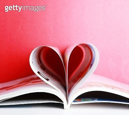 Close-Up Of Heart Shape Made With Pages On Table Against Red Wall - gettyimageskorea