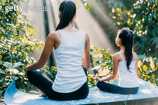 Asian mother  and daughter meditating in lotus position in rainforest in Bali, Indonesia - gettyimageskorea