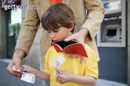 Father and Son Putting Money in Wallet - gettyimageskorea