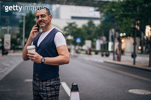 One handsome, mature man is standing on the street, holding takeaway coffee and talking on phone. - gettyimageskorea