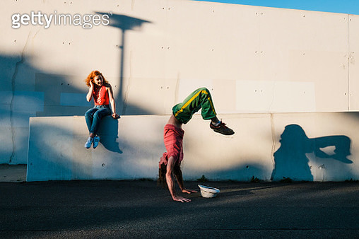 Young woman watching man do handstand along urban wall - gettyimageskorea