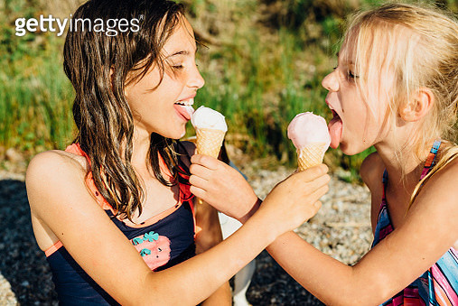 Two girls eating icecream on the beach - gettyimageskorea