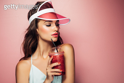 Fashion pretty cool girl drinks from cup over pink background - gettyimageskorea