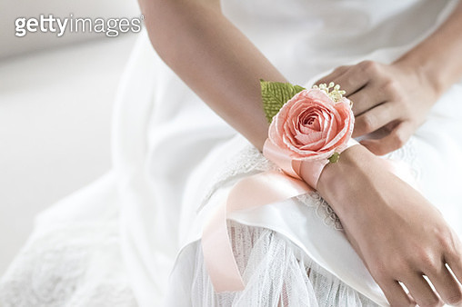 Midsection Of Bride With Floral Patterned Bracelet Sitting Over Against White Background - gettyimageskorea