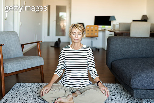 Mature woman practicing yoga at home - gettyimageskorea