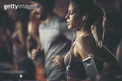 Young female athlete listening music while running on treadmill in a gym. - gettyimageskorea