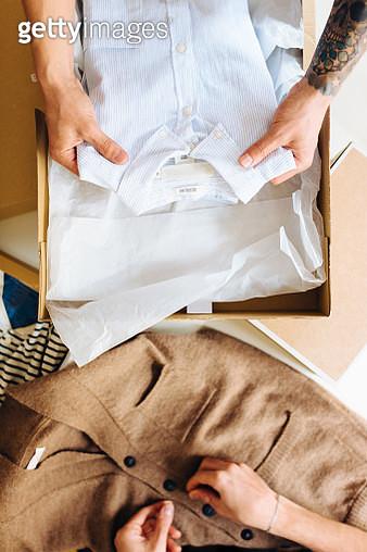 Men folding clothes into boxes - gettyimageskorea