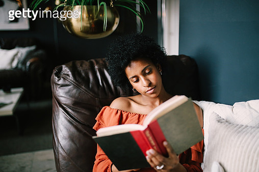 Portrait of a young woman relaxing and reading in her Downtown Los Angeles apartment - gettyimageskorea