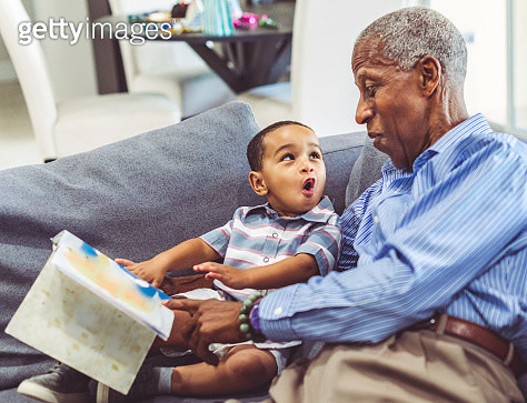 African American grandchild and grandfather read a book together at home - gettyimageskorea