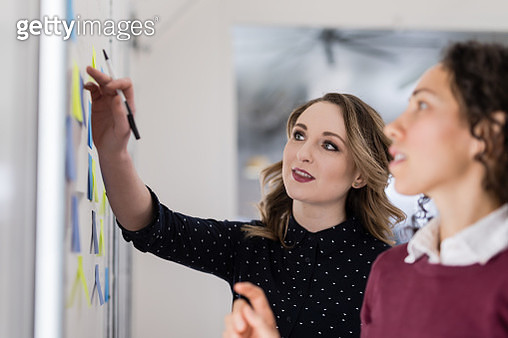 Female colleagues going over business strategy - gettyimageskorea