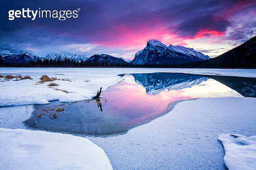 Pink sunrise over mountain reflected in partially frozen lake with snow - gettyimageskorea