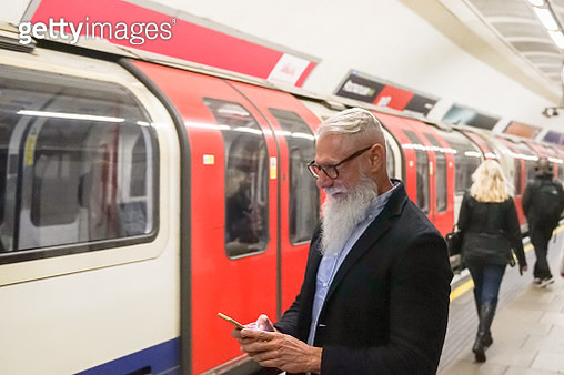 View of a attractive business man using smartphone. Cheerful smiling pensioner using smartphone having video call waiting in metro station of city. Tech and joyful elderly lifestyle  - Image - gettyimageskorea