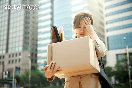 Fired businesswoman carrying box of personal items - gettyimageskorea